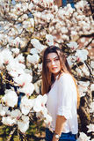 Outdoor portrait of a young beautiful woman near magnolia tree with flowers. Girl wearing stylish clothes. Female spring mood Royalty Free Stock Photo