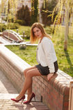 Outdoor portrait of young beautiful woman posing on street in sunny day. Female fashion. City lifestyle. Stock Photography