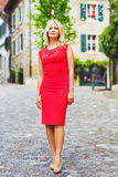 Outdoor portrait of young blond woman. Wearing red dress Stock Image