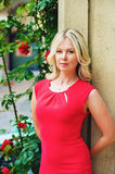Outdoor portrait of young blond woman. Wearing red dress, arms behind the back, leaning on the wall Royalty Free Stock Images