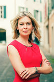Outdoor portrait of young blond woman. Wearing red dress, arms crossed, toned image Royalty Free Stock Photography