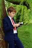 Outdoor portrait of boy going to First Holy Communion. Outdoor portrait of young boy in dark suit going to First Holy Communion stock photos