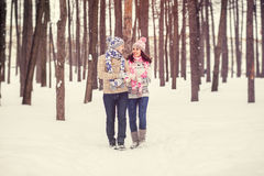 Outdoor portrait of young cheerful teen girl and guy  walking in winter time. Hipster couple  in love hugging . Valentines day. Stock Image