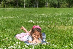 Outdoor portrait of young child girl reading a book on natural b Royalty Free Stock Photography