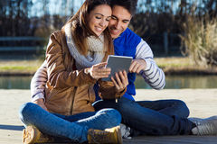 Outdoor portrait of young couple with digital tablet Royalty Free Stock Images