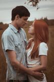 Outdoor   portrait of young couple kissing in summer field Stock Photo