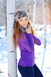 Outdoor portrait of young girl in winter park. Woman sitting in Royalty Free Stock Photo