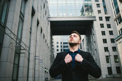 Outdoor portrait of young handsome man with a beard against the backdrop of modern architecture. Royalty Free Stock Images