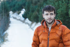 Outdoor portrait of young handsome man wearing beard and orange winter down jacket Royalty Free Stock Image