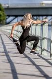 Young happy blonde girl doing sport in the city. Outdoor portrait of young happy blonde girl doing sport in the city, urban background Royalty Free Stock Image