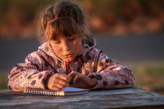 Outdoor portrait of young happy child girl drawing or writing in. Park on natural background stock photo