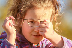 Outdoor portrait of young happy child girl wearing eye glasses o Stock Images
