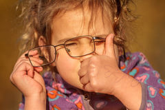 Outdoor portrait of young happy child girl wearing eye glasses o Royalty Free Stock Photos