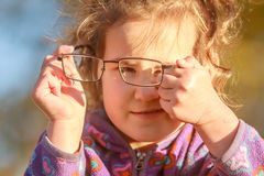 Outdoor portrait of young happy child girl wearing eye glasses o Stock Image