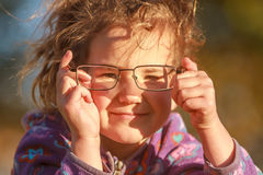 Outdoor portrait of young happy child girl wearing eye glasses o Royalty Free Stock Photography