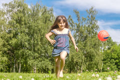 Outdoor portrait of young happy girl playing will ball on natura Stock Image
