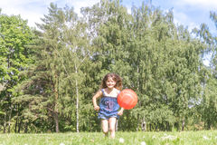 Outdoor portrait of young happy girl playing will ball on natura Royalty Free Stock Photos
