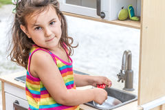 Outdoor portrait of young happy smiling girl playing toy kitchen. At playground in park Stock Image