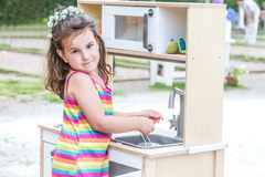 Outdoor portrait of young happy smiling girl playing toy kitchen Royalty Free Stock Images