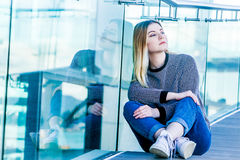 Outdoor portrait of young happy smiling teen girl on a glass bri Royalty Free Stock Image