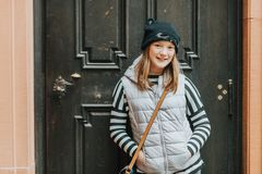 Outdoor portrait of young kid girl wearing grey sleeveless down jacket. And black hat with cat ears royalty free stock photo