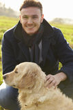 Outdoor Portrait Of Young Man With Golden Retriever Stock Image