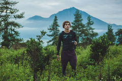 Outdoor portrait of Young man looking on Batur volcano and Agung. Mountain view at morning from Kintamani, Bali, Indonesia and drink water Royalty Free Stock Photos