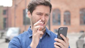 Outdoor Portrait of Young Man Upset by Loss while Using Smartphone. 4k high quality, 4k high quality stock footage