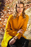 Outdoor portrait of young model wearing coat posing in the autumn park. Royalty Free Stock Photos