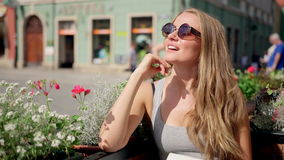Outdoor portrait of young pretty blonde girl wearing retro round sunglasses sitting alone at old city cafe and waiting for a frien Stock Photos