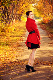 Outdoor portrait of young redheaded woman in autumn forest. Wearing red coat and black belt royalty free stock photos