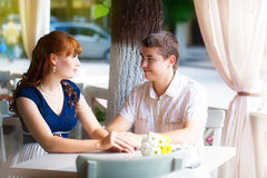 Outdoor portrait of young sensual couple in summer cafe. Love an Stock Photos