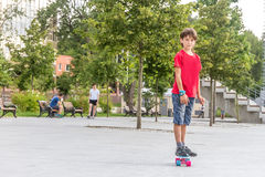 Outdoor portrait of young smiling teenager boy riding short mode Royalty Free Stock Photo