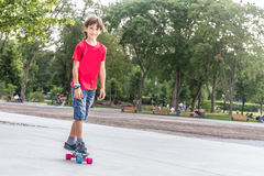 Outdoor portrait of young smiling teenager boy riding short mode Stock Photography