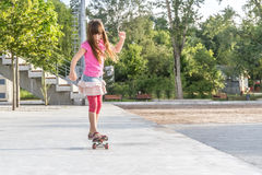 Outdoor portrait of young smiling teenager girl riding skateboar Royalty Free Stock Image
