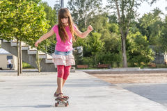 Outdoor portrait of young smiling teenager girl riding skateboar Royalty Free Stock Photos