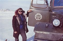 Outdoor portrait of young soviet driver near his truck. Chukchi Peninsula, USSR - March 1979:Outdoor portrait of young soviet driver near his truck Royalty Free Stock Image