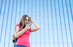 Portrait of young teenager brunette girl in coral t-shirt with long hair. girl on city looking on the smart phone. Glass building. Outdoor portrait of young royalty free stock photos