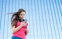 Portrait of young teenager brunette girl in coral t-shirt with long hair. girl on city looking on the smart phone. Glass building. Outdoor portrait of young royalty free stock photography