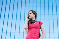 Portrait of young teenager brunette girl in coral t-shirt with long hair. girl on city talking on the smart phone. Glass building. Outdoor portrait of young royalty free stock images