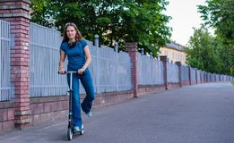 Portrait of young teenager brunette girl with long hair driving scooter on city street royalty free stock photos