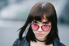 Outdoor portrait of a young and very beautiful brunette with big blue eyes in a pink glasses on the blurred background. Outdoor portrait of a young and very Stock Photos
