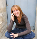 Outdoor portrait young woman. Talk on a cellular telephone Stock Images