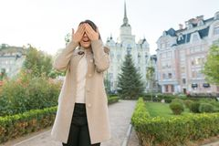 Outdoor portrait of a young woman covering her eyes stock photography