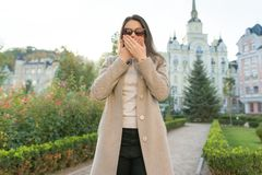Outdoor portrait of a young woman covering her mouth with hands royalty free stock photos