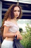 Outdoor portrait of young woman near bridge. Portrait of young woman near bridge stock photo