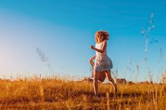 Outdoor portrait of young woman with red curly hair running with a bag of flowers. Happy summer holidays. Positive girl having fun Stock Photos