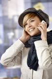 Outdoor portrait of young woman talking on mobile. Phone in winter sunshine Stock Image