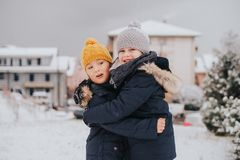 Outdoor portrait of young 6 year old boys wearing warm jacket. And boots, enjoying winter time Stock Photos