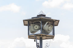 Outdoor public address loudspeakers against a blue Royalty Free Stock Photo